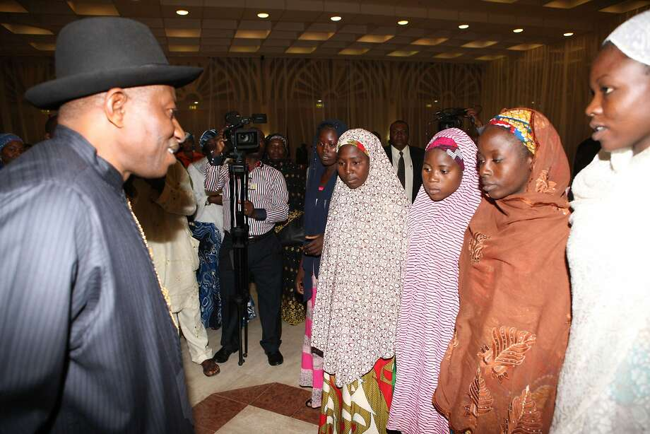 Nigerian President Goodluck Jonathan (L) speaks to some of the Chibok schoolgirls who escaped Islamist captors and relatives of the hostages during a meeting at the presidency in Abuja on July 22, 2014. A delegation of more than 150 people from Chibok, including some of the 57 girls who escaped their Islamist captors, parents of the hostages as well as Chibok community leaders, met President Goodluck Jonathan and other top officials of the government for the first time since the girls were seized. AFP PHOTO / WOLE EMMANUELWOLE EMMANUEL/AFP/Getty Images Photo: Wole Emmanuel, AFP/Getty Images