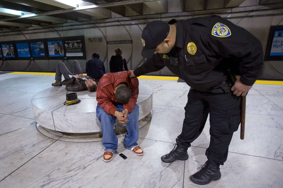 BART police officer Jesse Sekhon, right, tries to wake a sleeping New Years reveler at Embarcadero Station in downtown San Francisco, Calif. on Friday, Jan. 1, 2010, before the last train leaves after 3 a.m.