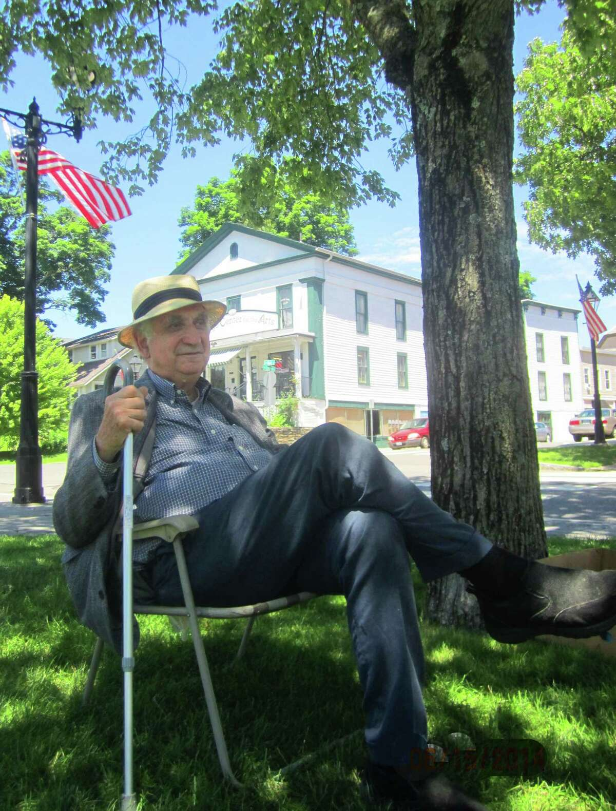 Richard Salter of Gaylordsville takes grateful advantage of a break between patrons to relax during the 19th annual Outdoor Art Festival, hosted June 14-15, 2014 on the Village Green by the New Milford Historical Society.