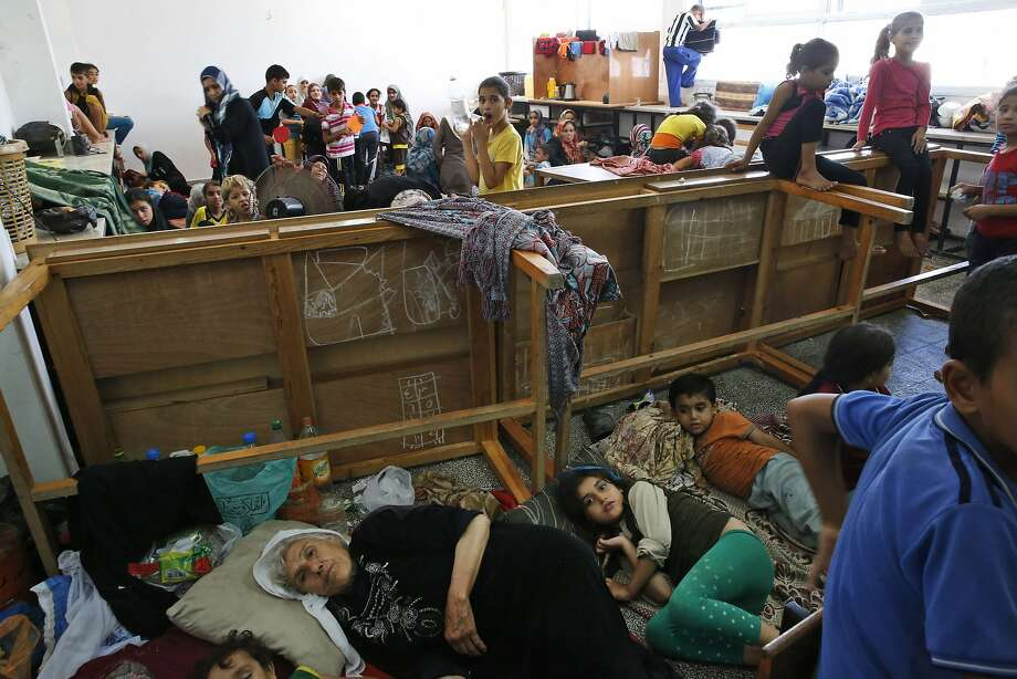 Palestinian families take refuge at a U.N. school after fleeing their homes following Israeli air strikes in Beit Hanoun, northern Gaza Strip. Photo: Lefteris Pitarakis, Associated Press