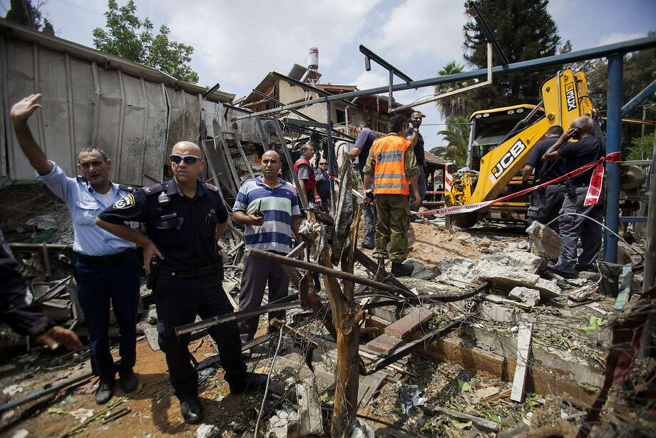 Israeli police officers secure a destroyed house that was hit by a rocket fired by Palestinians militants from Gaza, in Yahud, a Tel Aviv suburb near the airport, central Israel, Tuesday, July 22, 2014. As a result, Delta Air Lines and U.S. Airlines decided to cancel their scheduled flights to Israel.(AP Photo/Dan Balilty) Photo: Dan Balilty, Associated Press