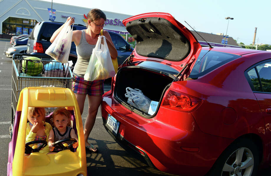 Colleen Caceres, of Stratford, loads groceries into her car as her children Zoe, 4, and Dante, 1, wait in the cart at the Stop and Shop supermarket off of East main Street in Stratford, Conn. on Tuesday July 22, 2014. Several fruits, like peaches, are being recalled at some chain stores like Stop & Shop, Trader Joe's, and Sam's Club because of listeria. Photo: Christian Abraham / Connecticut Post