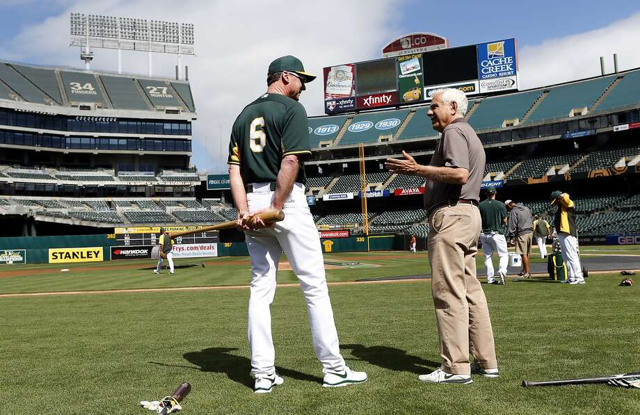Oakland A's manager Bob Melvin (left) chats on the field with team co-owner Lew Wolff, who has accepted the new lease, before the team plays the Houston Astros at O.co Coliseum. Photo: Scott Strazzante, The Chronicle