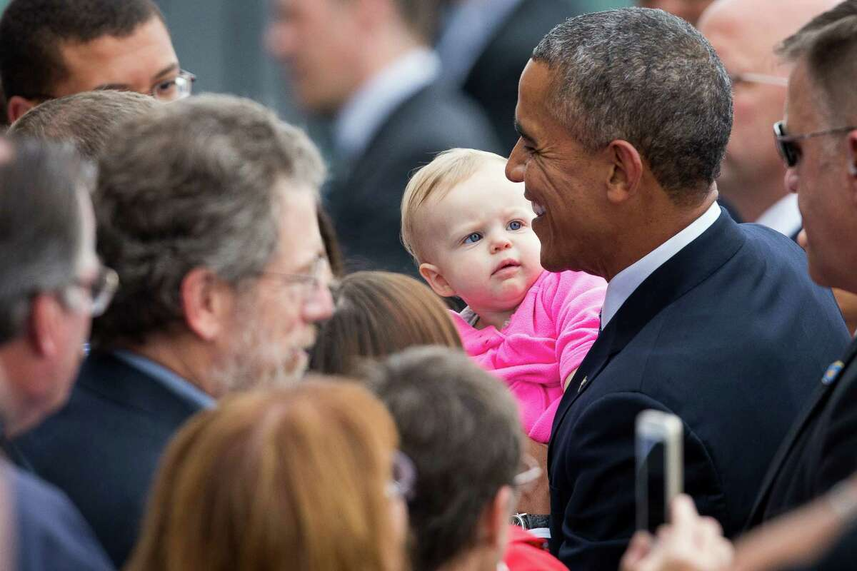President Barack Obama holds Ava Cunnington, 11 months old, in the crowd after arriving at King County International Airport at around 3:15 pm for a fundraising visit on July 22, 2014.