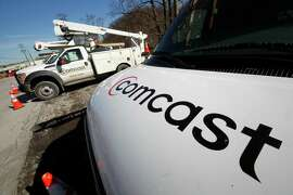 FILE - This Feb. 15, 2011 file photo shows Comcast installation trucks in Pittsburgh. Comcast Corp. reports quarterly financial results before the market opens Tuesday, July 22, 2014. (AP Photo/Gene J. Puskar, File) ORG XMIT: NYBZ155