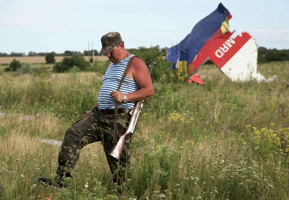 A pro-Russian fighter walks past a piece of the crashed Malaysia Airlines Flight 17 near the village of Hrabove, eastern Ukraine Monday, July 21, 2014. Four days after Flight 17 was shot out of the sky, international investigators still have had only limited access to the crash site, hindered by pro-Russia fighters who control the verdant territory in eastern Ukraine. Outrage over the delays and the possible tampering of evidence at the site was building worldwide, especially in the Netherlands, where most of the victims were from. (AP Photo/Dmitry Lovetsky) Photo: Dmitry Lovetsky, STF / AP