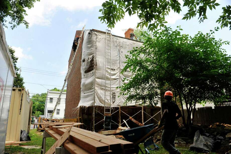 Workers with Yankee Construction out of Mountainville, N.Y., work on the Stephen & Harriet Myers House, on Tuesday, July 22, 2014, in Albany, N.Y.  (Paul Buckowski / Times Union) Photo: Paul Buckowski / 00027883A