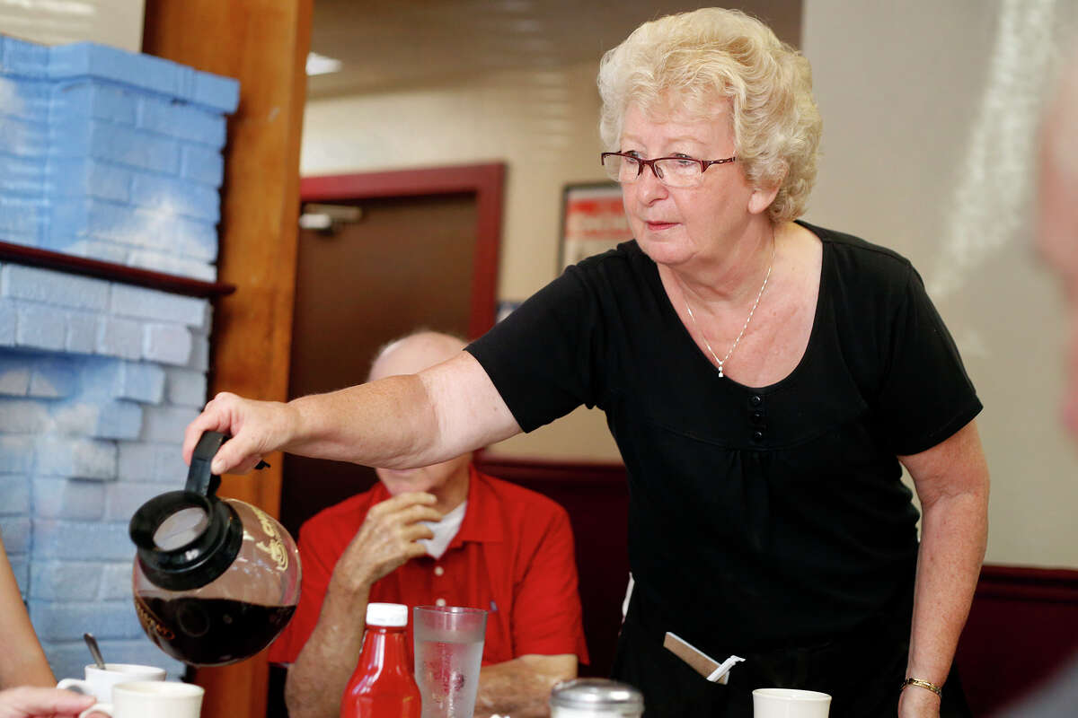 Wanda Cross pours coffee for the First United Methodist Church Mens Club inside the Four Corners Luncheonette on Tuesday, July 22, 2014 in Delmar, N.Y. The group has met for breakfast at Four Corners on Tuesdays for several decades. Wanda has been an employee at the restaurant for 26 years. (Tom Brenner/ Special to the Times Union)