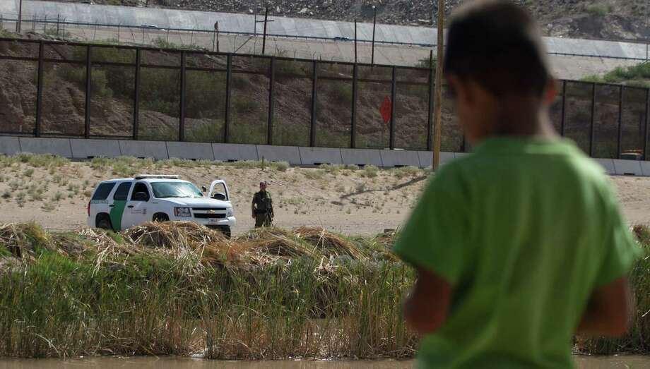 A Mexican boy looks at a member of the U.S. Border Patrol standing guard on the border between El Paso in the United States and Ciudad Juarez in Mexico, Photo: JESUS ALCAZAR, Stringer / AFP