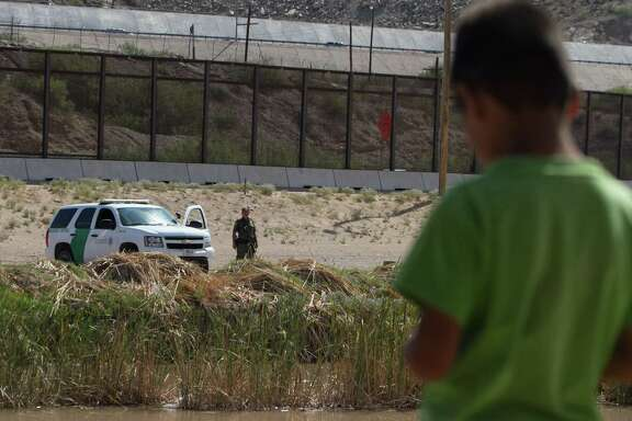 A Mexican boy looks at a member of the U.S. Border Patrol standing guard on the border between El Paso in the United States and Ciudad Juarez in Mexico,