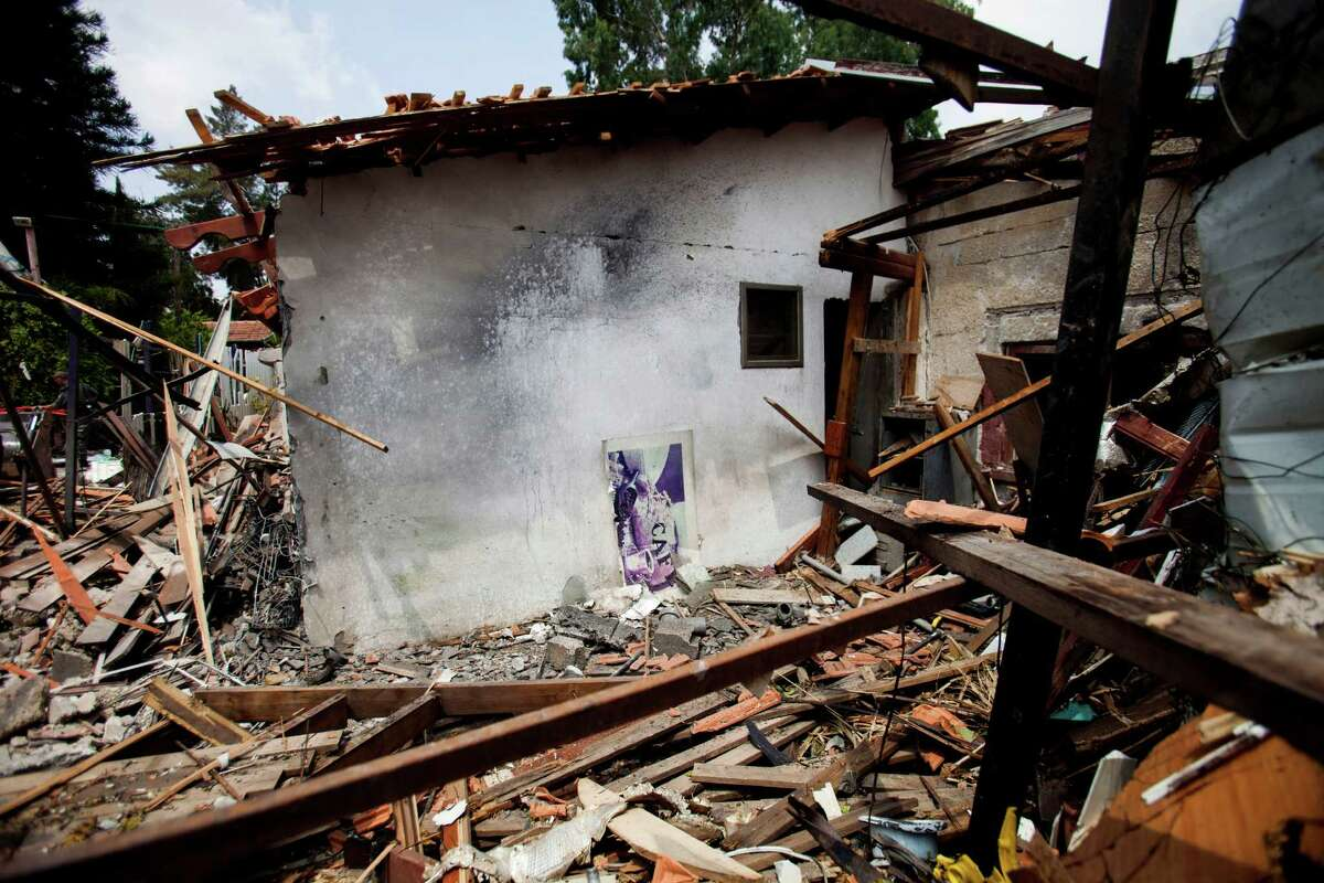A destroyed house that was hit by a rocket fired by Palestinians militants from Gaza, in Yahud, a Tel Aviv suburb near the airport, central Israel, Tuesday, July 22, 2014. As a result, Delta Air Lines and U.S. Airlines decided to cancel their scheduled flights to Israel.(AP Photo/Dan Balilty) ORG XMIT: DB102