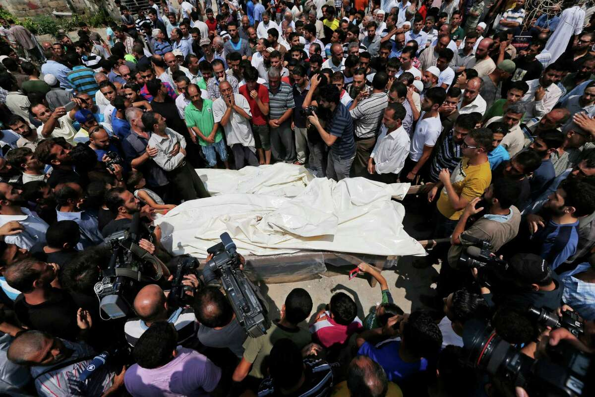 Mourners gather around the bodies of seven members of the Kelani family, killed overnight by an Israeli strike in Gaza City, during their funeral in Beit Lahiya, northern Gaza Strip, on Tuesday, July 22, 2014. Ibrahim Kelani, 53, his wife Taghreed and their five children, were killed in the strike on a Gaza City highrise. Ibrahim's brother Saleh Kelani said Tuesday that his brother and his brother?'s children, ranging in age from four to 12, had German citizenship, while his wife had not. The family had rented the apartment in the high-rise after fleeing their home in the northern Gaza town of Beit Lahiya which came under heavy shelling by the Israeli army. (AP Photo/Lefteris Pitarakis) ORG XMIT: AXLP120