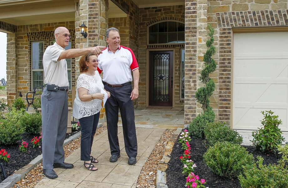Homebuyers Judy and Dennis Capilongo look at new home landscaping features with their realtor, Mike Roller, in front of the Chesmar model homes in Lakecrest Park subdivision in Katy. Photo: Diana L. Porter, Freelance / © Diana L. Porter