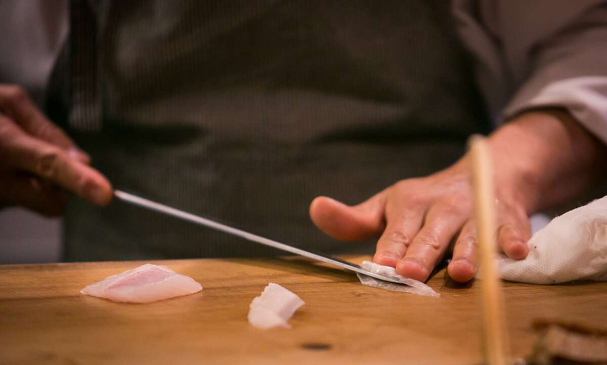 Chef Mitsunori Kusakabe slices fish at Kusakabe in San Francisco, Calif., on Saturday, July 19th, 2014.