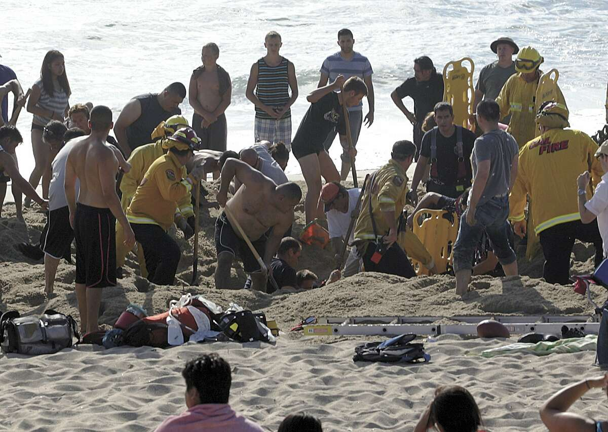 This Monday, July 21, 2014, photo released by the Half Moon Bay Review shows emergency crew workers and volunteers working to rescue a man at Francis State Beach in Half Moon Bay, Calif. Authorities say a young man has died after a hole he dug on a Northern California beach collapsed and trapped him in the sand for at least five minutes.