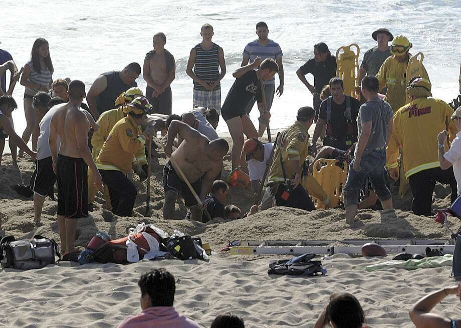 This Monday, July 21, 2014, photo released by the Half Moon Bay Review shows emergency crew workers and volunteers working to rescue a man at Francis State Beach in Half Moon Bay, Calif. Authorities say a young man has died after a hole he dug on a Northern California beach collapsed and trapped him in the sand for at least five minutes. Photo: Dean Coppola, Associated Press