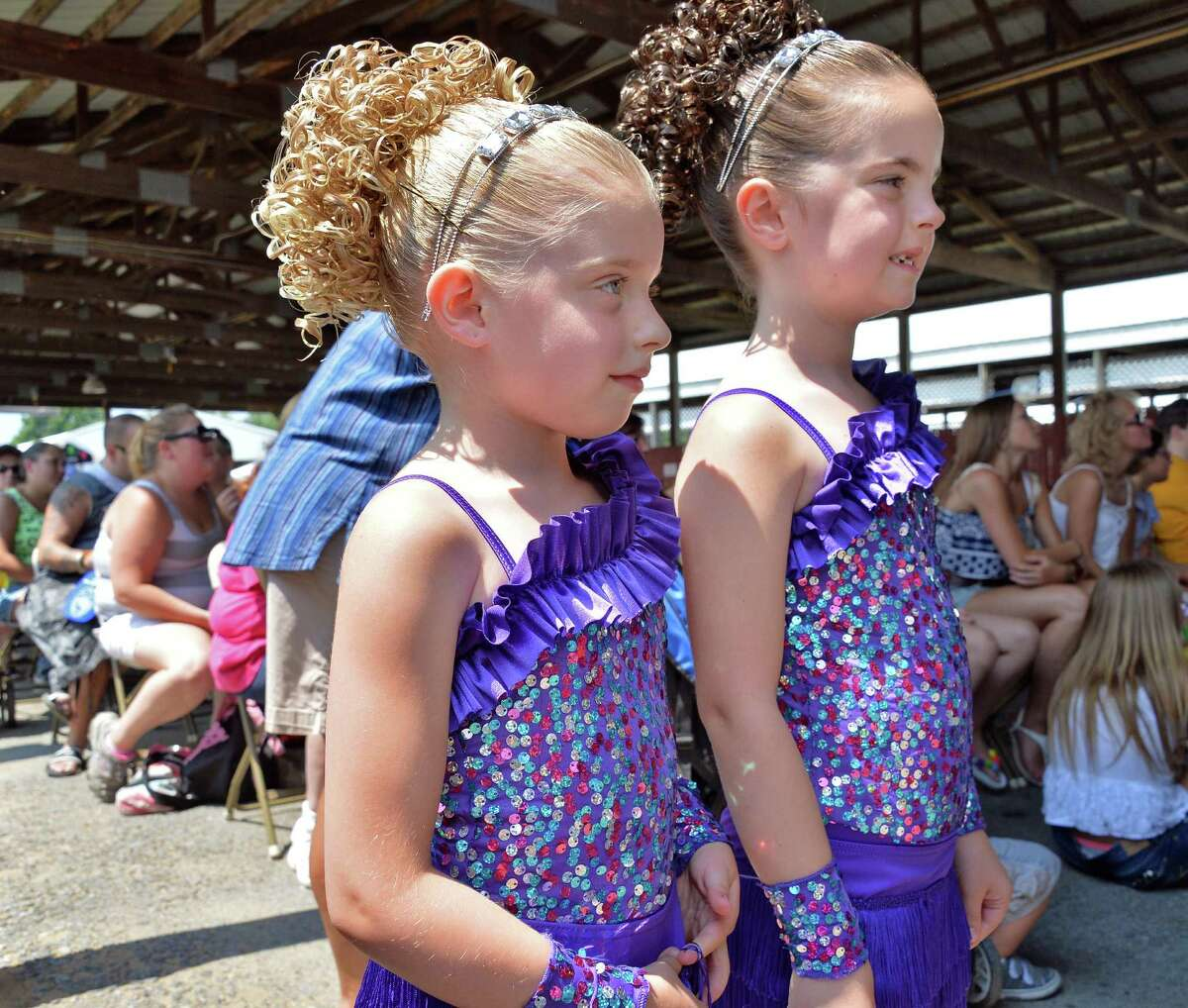 Emily Hye, 5, left, and Alyson O'Connor,6, of Ballston Spa watch the competition as they wait their turn in the under 7 talent show on opening day of the Saratoga County Fair Tuesday July 22, 2014, in Ballston Spa, NY. (John Carl D'Annibale / Times Union)