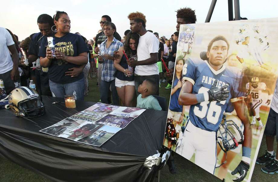 Vivian Cuffin-Meade (second from left), the mother of Joshua Biggles, is comforted by her husband, Daryl Meade, during the candlelight vigil for the O'Connor High School football player held on the football field he was so familiar with. Photo: Kin Man Hui, San Antonio Express-News / ©2014 San Antonio Express-News