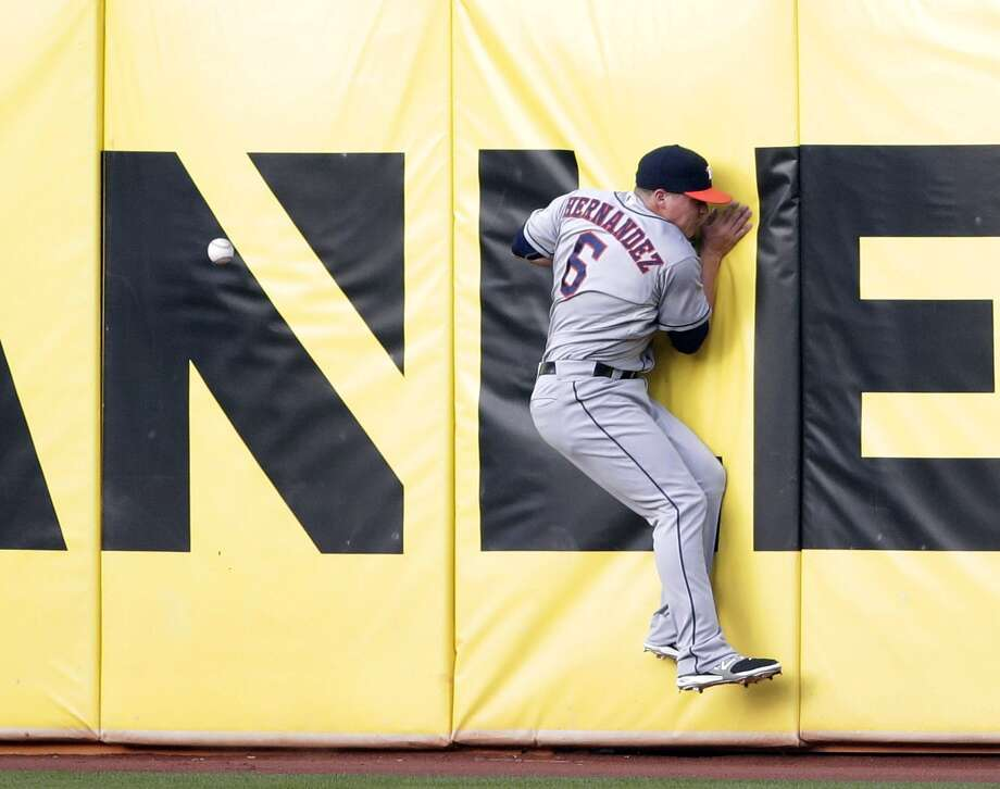 Astros right fielder Kiké Hernandez hits the wall while chasing a drive from the Athletics' Yoenis Cespedes during the first inning Tuesday night. Cespedes ended up with a double but didn't score in the inning. Photo: STF / AP