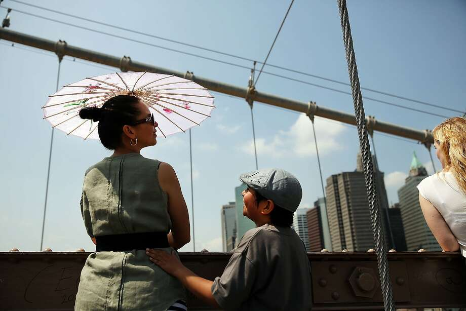 NEW YORK, NY - JULY 22: A woman and child watch police activity on the Brooklyn Bridge following a pair of white flags that appeared overnight atop the two towers of the Brooklyn Bridge replacing the American flags on July 22, 2014 in New York City. Police are investigating the incident which turned one of New York's iconic pieces of architecture into a police investigation scene as hundreds of curious people looked on. (Photo by Spencer Platt/Getty Images) Photo: Spencer Platt, Getty Images