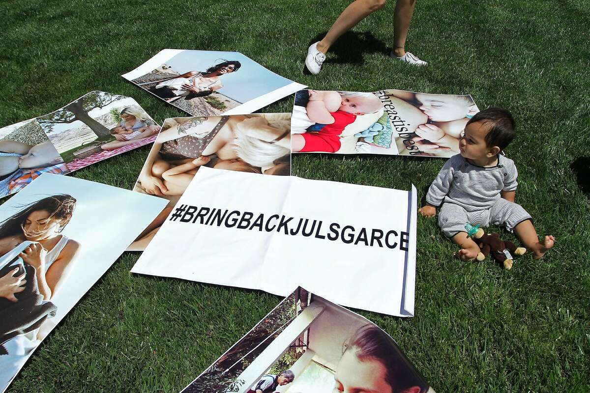 Lila Jaigirdar sits on the lawn in front of Facebook as her mother Mandee puts up photos that were removed from Instagram on Monday, July 22, 2014 in Menlo Park, Calif. Instagram's removal of photos depicting breastfeeding women has sparked outrage among users.