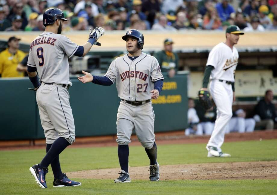 Jose Altuve (27) celebrates with teammate Marwin Gonzalez (9) after they both scored during the third inning. Photo: Associated Press