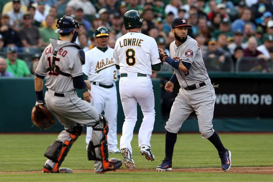 The Athletics' Jed Lowrie (8) is tagged out by Marwin Gonzalez, right, in a rundown between third and home in the third inning. Photo: RAY CHAVEZ, McClatchy-Tribune News Service
