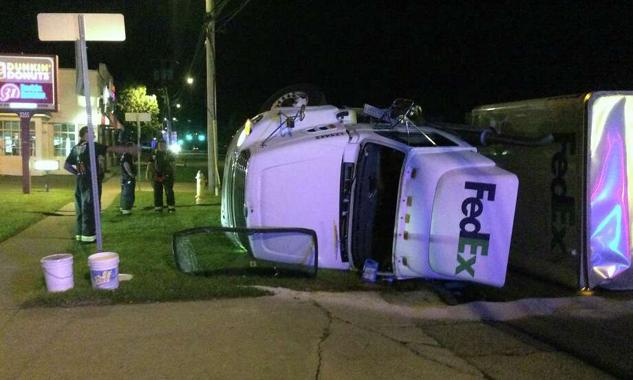 A FedEx tandem tractor-trailer partially overturned after colliding with an SUV on the Post Road early Wednesday. Photo: Fairfield Fire Department / Fairfield Citizen