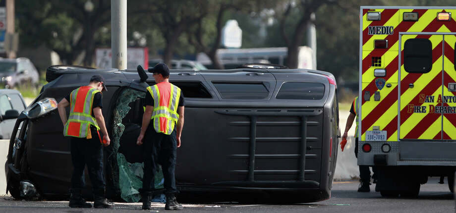 San Antonio Fire Department paramedics monitor the scene of a rollover accident involving a minivan Wednesday July 23, 2014 shortly after 9 a.m. on the northbound lanes of the 16,000 block of U.S. Highway 281 North between Brook Hollow and Thousand Oaks. Police at the scene said the van skidded out of control hitting the center barrier and that there were no serious injuries. Traffic flowing north was backed up for about an hour. Photo: JOHN DAVENPORT, San Antonio Express-News / ©San Antonio Express-News/John Davenport
