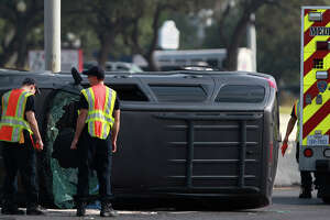 San Antonio Fire Department paramedics monitor the scene of a rollover accident involving a minivan Wednesday July 23, 2014 shortly after 9:00 a.m. on the northbound lanes of the 16,000 block of U.S. Highway 281 North between Brook Hollow and Thousand Oaks. Police at the scene said the van skidded out of control hitting the center barrier and that there were no serious injuries. Traffic flowing north was backed up for about an hour.