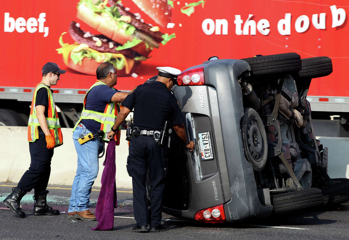San Antonio police, Fire Department paramedics and firefighters monitor the scene of a rollover accident involving a minivan Wednesday July 23, 2014 shortly after 9 a.m. on the northbound lanes of the 16,000 block of U.S. Highway 281 North between Brook Hollow and Thousand Oaks. Police at the scene said the van skidded out of control hitting the center barrier and that there were no serious injuries. Traffic flowing north was backed up for about an hour.