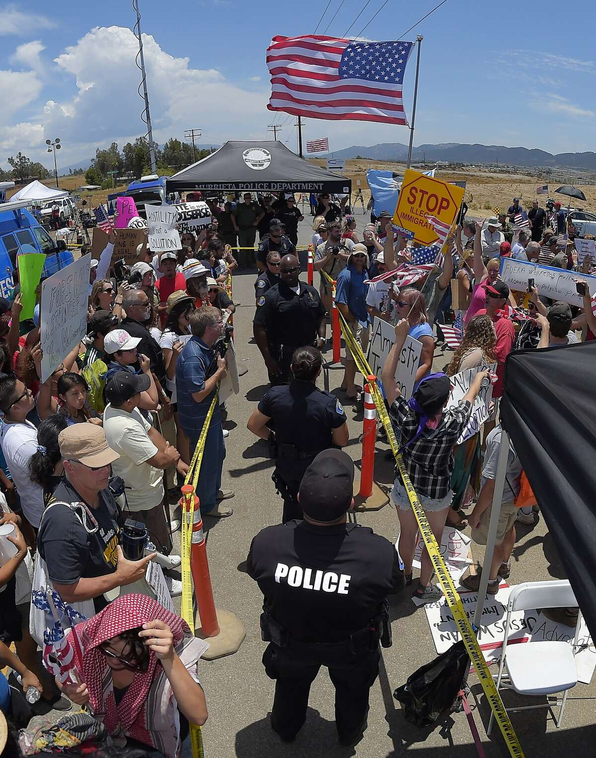Demonstrators from opposing sides confront each other while being separated by Murrieta police officers, Friday, July 4, 2014, outside a U.S. Border Patrol station in Murrieta, Calif. Demonstrators on both sides of the immigration debate had gathered where the agency was foiled earlier this week in an attempt to bus in and process some of the immigrants who have flooded the Texas border with Mexico. (AP Photo/Mark J. Terrill)