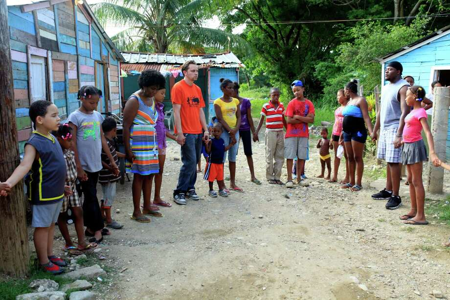 The Encounter Church mission team prays with the children of the San Cristobal community in the Dominican Republic. Photo: Contributed Photo, Contributed / Darien News Contributed