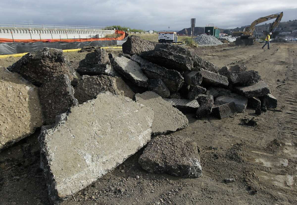Chunks of asphalt wait to be hauled away while a road crew demolishes the old San Pedro Creek bridge on Highway 1 in Pacifica, Calif. on Wednesday, July 23, 2014. North and southbound traffic on the Coast Highway is being diverted during the project which, when completed in mid-2016, will include a seismically safe, longer and higher bridge over the creek to prevent potential flooding.