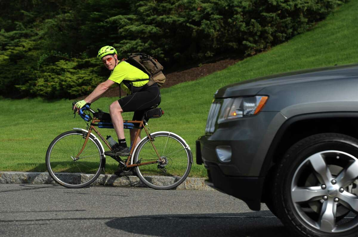 A biker in Danbury takes notice of the on-coming car.