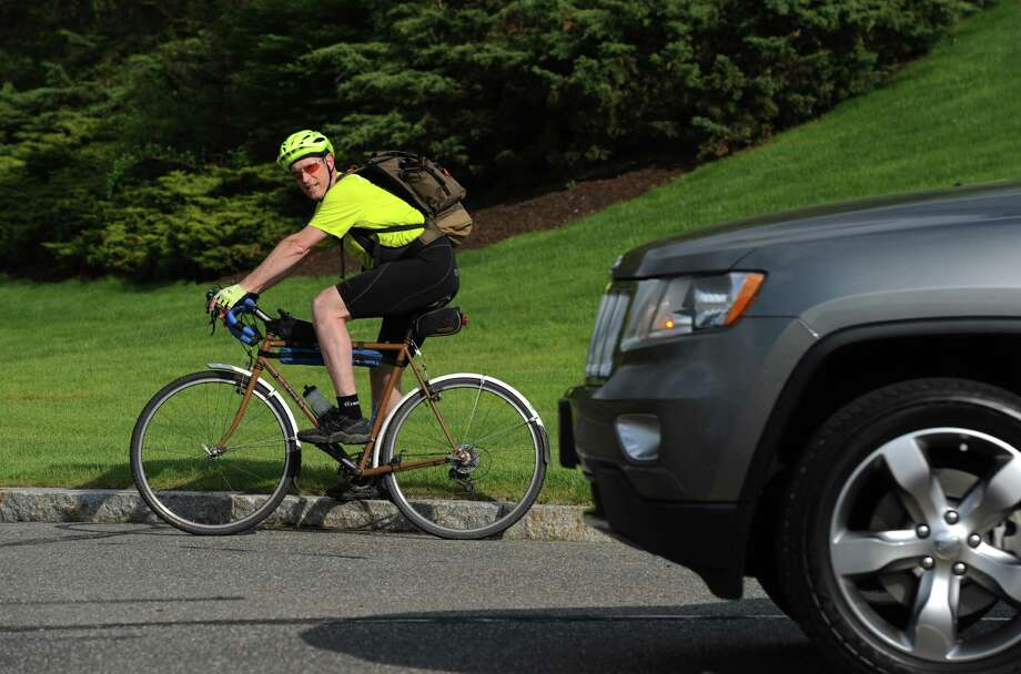 A biker in Danbury takes notice of the on-coming car. Photo: Tyler Sizemore / The News-Times