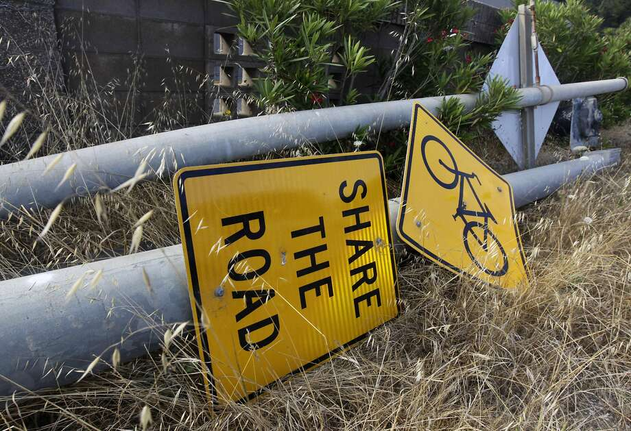 Traffic signs are stored on the side of the road while a construction crew demolishes the old San Pedro Creek bridge on Highway 1 in Pacifica, Calif. on Wednesday, July 23, 2014. North and southbound traffic on the Coast Highway is being diverted during the project which, when completed in mid-2016, will include a seismically safe, longer and higher bridge over the creek to prevent potential flooding. Photo: Paul Chinn, The Chronicle