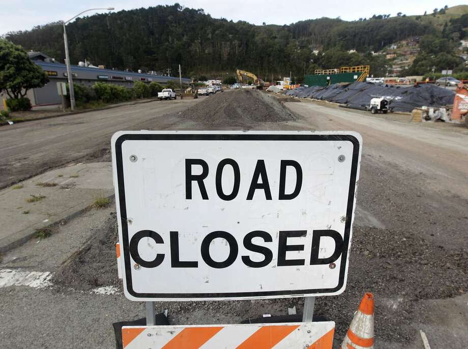 A long-term road closure remains in place while a contruction crew demolishes the old San Pedro Creek bridge on Highway 1 in Pacifica, Calif. on Wednesday, July 23, 2014. North and southbound traffic on the Coast Highway is being diverted during the project which, when completed in mid-2016, will include a seismically safe, longer and higher bridge over the creek to prevent potential flooding. Photo: Paul Chinn, The Chronicle