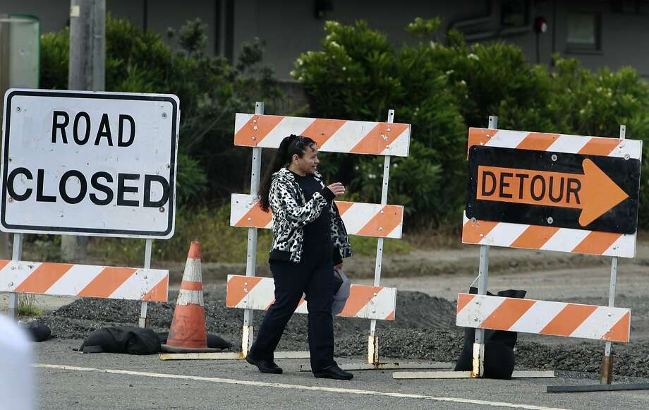 A woman crosses Highway 1 where a road crew is demolishing the old San Pedro Creek bridge in Pacifica, Calif. on Wednesday, July 23, 2014. North and southbound traffic on the Coast Highway is being diverted during the project which, when completed in mid-2016, will include a seismically safe, longer and higher bridge over the creek to prevent potential flooding. Photo: Paul Chinn, The Chronicle