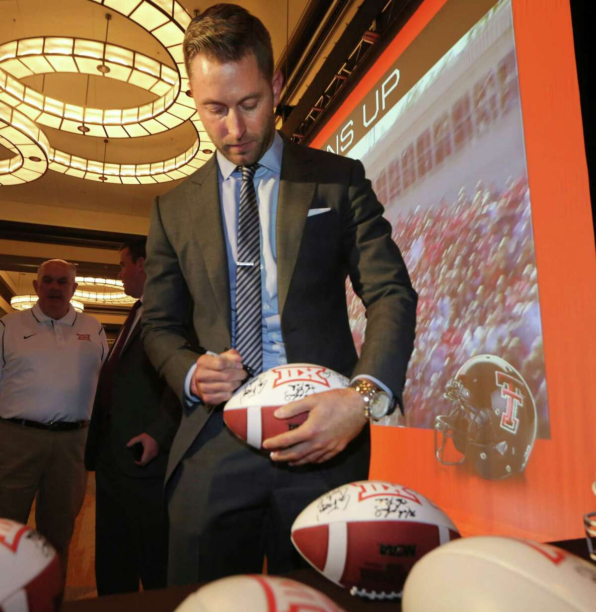 Proof the watch is fake ... Texas Tech football coach Kliff Kingsbury signs a football during the NCAA college Big 12 Conference football media days in Dallas, Monday, July 21, 2014. The watch seen on his wrist could be a $100 fake. (AP Photo/LM Otero)
