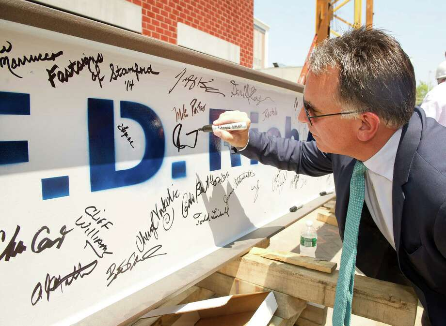 Tom Rich, CEO of F. D. Rich Company, signs a steel beam during a ceremony to commemorate the beginning of steel construction on Summer House, a 21-story building on lower Summer Street which will contain retail and restaurant space, 226 residential units and amenities including a pool. Photo: Lindsay Perry / Stamford Advocate
