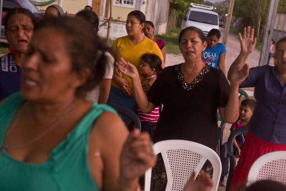 In this photo taken Saturday, July 19, 2014, Elsa Ramirez, 27, in yellow, deported from the United States with her children a day earlier, prays at a local outdoor church youth meeting, in Tocoa, Honduras. After her husband's death, Ramirez decided to head north. In less than a month's time and many thousands of miles later, a U.S. Immigration and Customs Enforcement flight brought Ramirez back to where she started. Ramirez does not know what the future will bring. She could hide out in her mother's home for a time, she said, perhaps work as a cook. (AP Photo/Esteban Felix) Photo: Esteban Felix, Associated Press