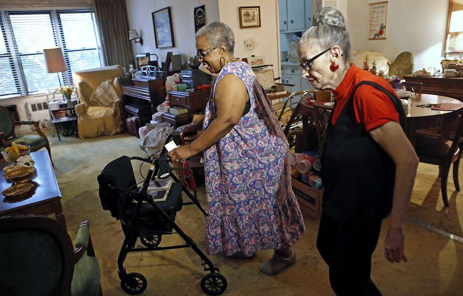 Carolyn Allen (left) makes her way to the living room with roommate Marcia Rosenfeld in New York. Photo: Kathy Willens, Associated Press