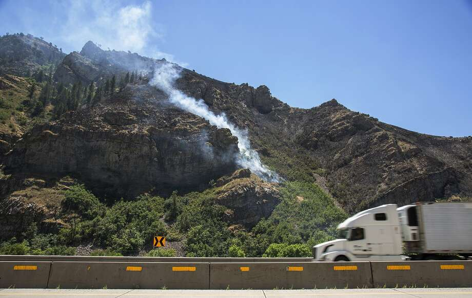 A wildfire burns Tuesday east of Morgan, Utah. Slightly cooler weather on Tuesday helped crews gain ground on the Tunnel Hollow Fire, which investigators believe was ignited by lightning. Photo: Benjamin Zack, Associated Press