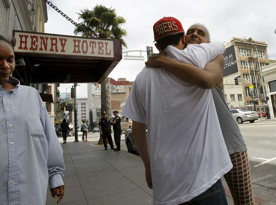 Friends of the victims hug at the site of the second shooting on Sixth Street near the Henry Hotel. Photo: Brant Ward, San Francisco Chronicle