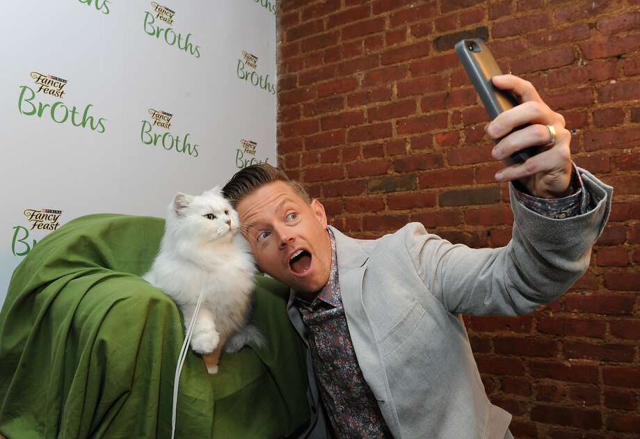 It's all about me ...ow: Chef Richard Blais takes a selfie with the Fancy Feast cat while hosting the Fancy Feast Broths launch party at the Tasting Table Test Kitchen in New York. Photo: Diane Bondareff, Associated Press