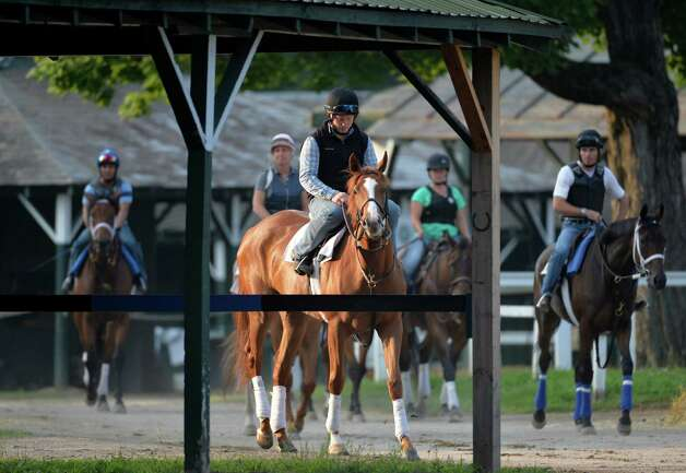 Horses are framed by a barn as they head to the main track early Wednesday morning July 23, 2014 during exercise time on the main track at the Saratoga Race Course in Saratoga Springs. Photo: SKIP DICKSTEIN, ALBANY TIMES UNION