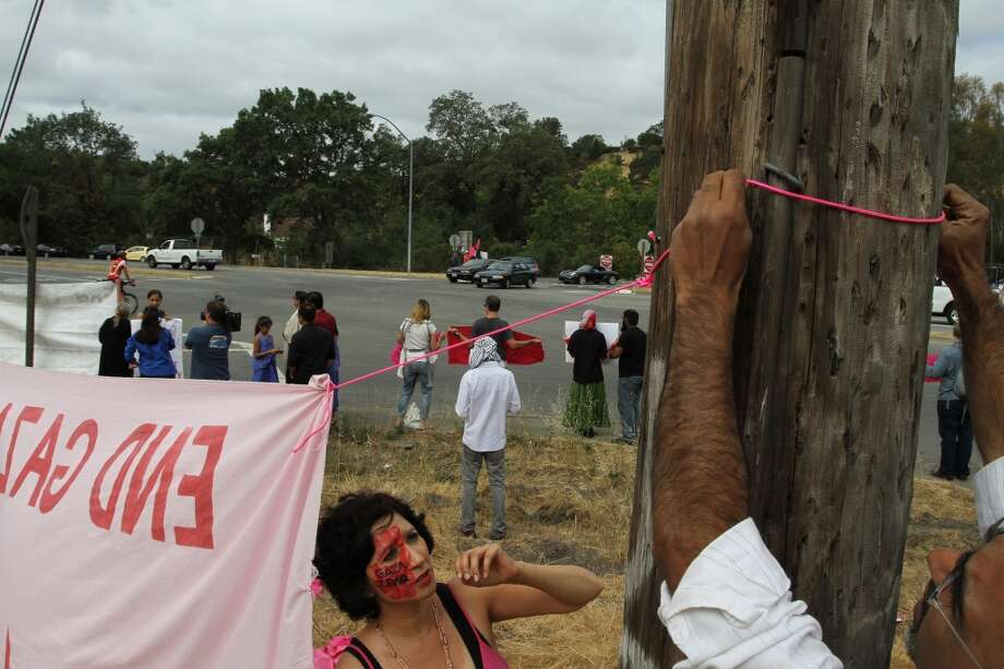 Nancy Mancias of Code Pink watches as Omar Nawaz puts up a flag on Page Mill Road. Photo: James Tensuan, The Chronicle