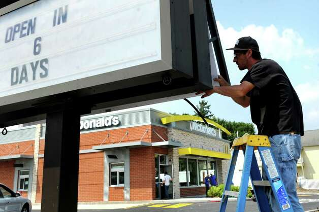 Electrician Bill Hubbell of Koval Electric works on the sign on Wednesday, July 23, 2014, at McDonald's in Waterford, N.Y. The business, which was ruined by a fire on Dec. 7, 2013, is due to open on July 29 at 11 a.m. The grand opening and flag raising with the Northside Fire District is scheduled for Aug. 6. (Cindy Schultz / Times Union) Photo: Cindy Schultz / 00027893A