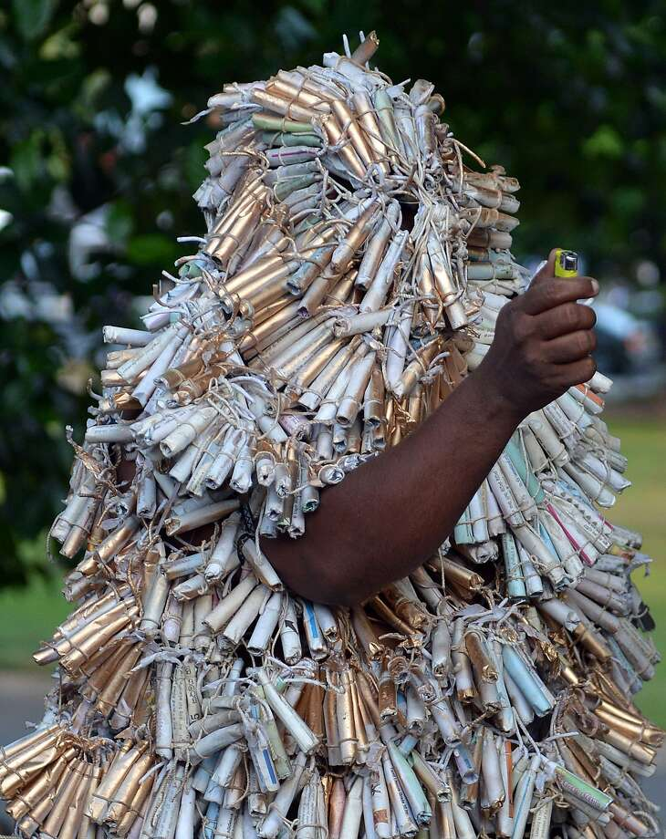 Firecracker man: In Colombo, an activist wrapped in firecrackers holds a lighter during a symbolic protest against 